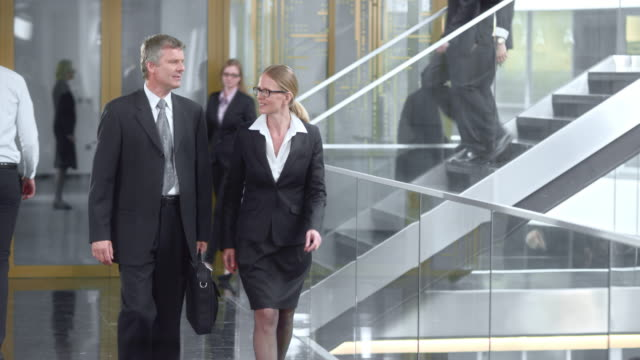 DS Business man and woman walking and talking video