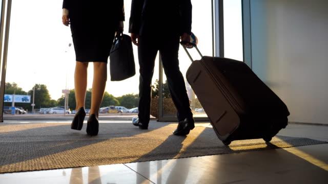 verksamhet man och kvinna med bagage går från flygplatsen till stadsgata. följ ung affärsman bära resväska på hjul och promenader med sin kvinnliga kollega från terminal hall. vy bakifrån närbild - affärsresa bildbanksvideor och videomaterial från bakom kulisserna