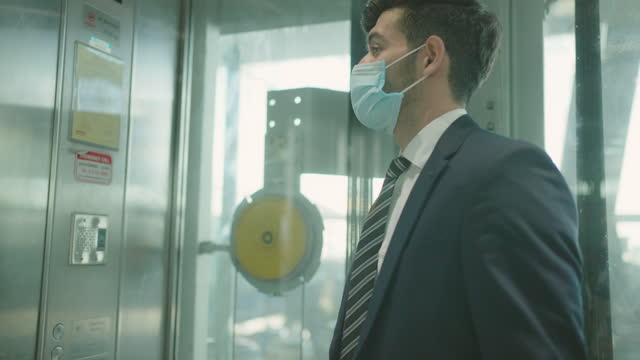 business man at airport elevator with mask.
