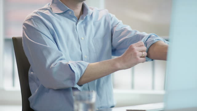 business man at office desk rolling up left sleeve, stretching fingers video