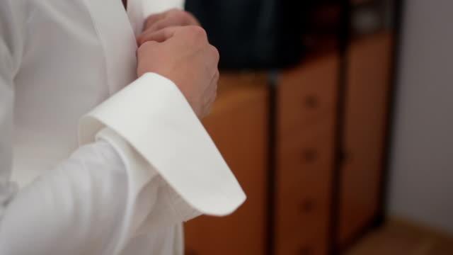 Business man buttoning shirt Business man buttoning shirt button down shirt stock videos & royalty-free footage