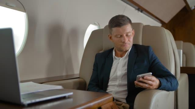 Chat de hombre de negocios en la cabina de jet privado - vídeo