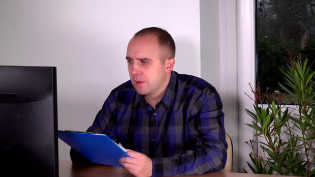 Business man checking clipboard documents looking at computer screen in office video