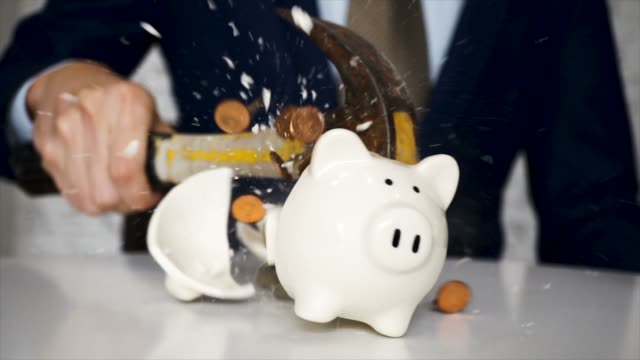 Business man Closeup breaking white piggy bank with a hammer and coins scattered everywhere in slow motion