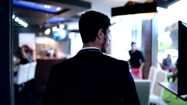 Business man comes to a meeting in restaurant Suave young man, wearing suit, walking through the restaurant. bar counter stock videos & royalty-free footage