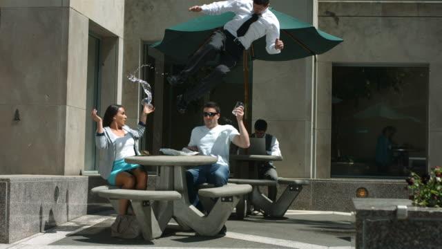 business mann flips auf tisch im hof - stuntman stock-videos und b-roll-filmmaterial