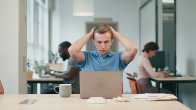 business man getting bad news by email. serious freelance man working on laptop - wine filmów i materiałów b-roll