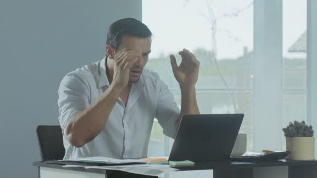 vídeos de stock, filmes e b-roll de homem de negócio que começ a notícia má. freelancer masculino deprimido que trabalha no portátil. - posição