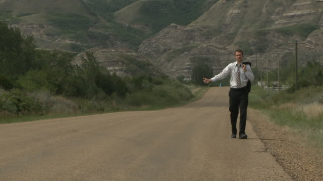 Business man hitch hiking on a lonely road video