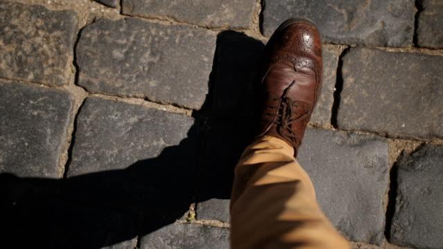 茶色の革靴を履いたビジネスマンが歩道を踏み、一人称でトップビュー。 - 主観視点点の映像素材/bロール