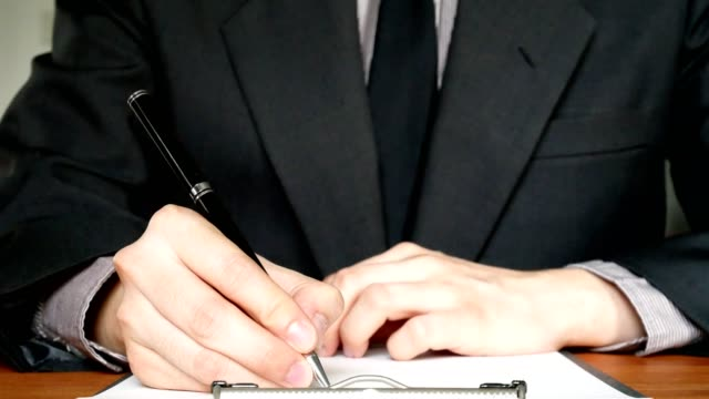 Business man in suit writing on document in office - close up shot video