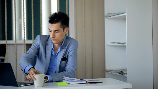 Business man is taking coffee break sitting at workplace continuing working video