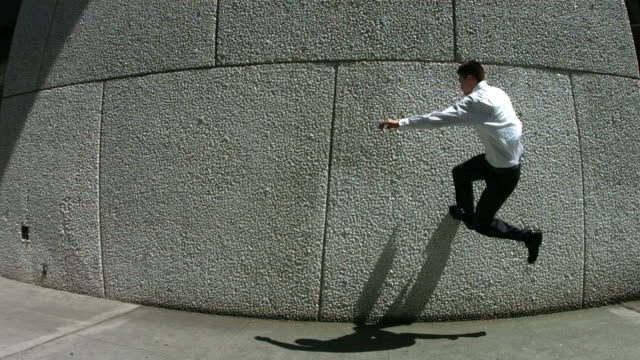Business man jumps off wall, slow motion video