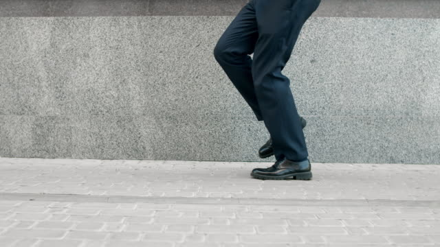 business man legs dancing at street. closeup shoes dancing outdoor near building - fare un passo video stock e b–roll