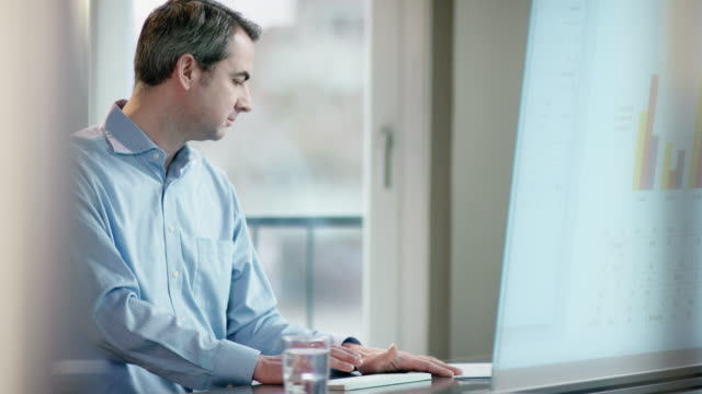 business man looking at screen, comparing data video