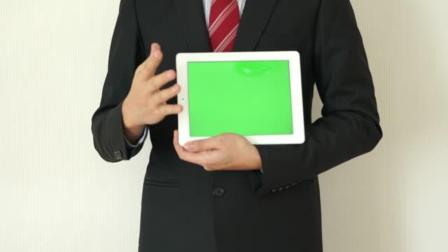 Business man present idea on Green Screen tablet video