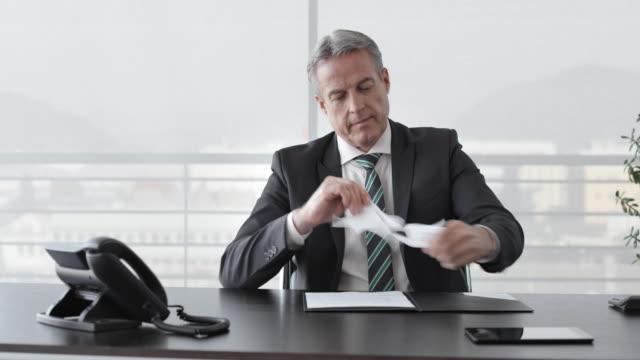 Hombre de negocios de DS leer y destrozando un documento - vídeo