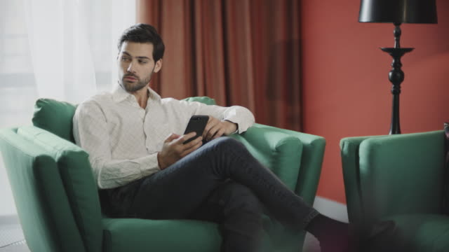 Business man scrolling mobile at luxury hotel. Businessman reading phone
