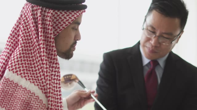 Business man showing his golf club to his arabic partner