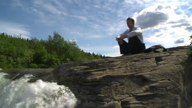 stockvideo's en b-roll-footage met business man sits at waterfalls - minder dan 10 seconden