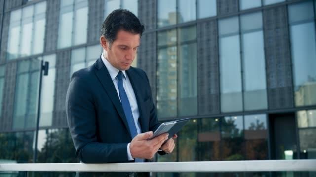 ds business man steht außerhalb des modernen geschäftsgebäudes und scrollt sein tablet - menschliche tätigkeit stock-videos und b-roll-filmmaterial