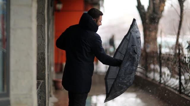 vídeos de stock e filmes b-roll de business man surviving the storm - chapéu