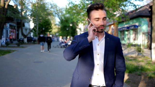 business man talking on mobile phone while walking down street city close-up video