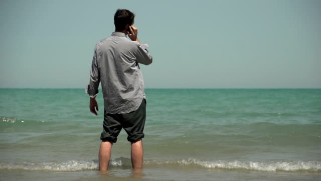 Business man talking on the phone, standing in ocean video