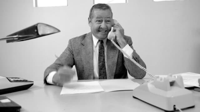 Business man talks on telephone video