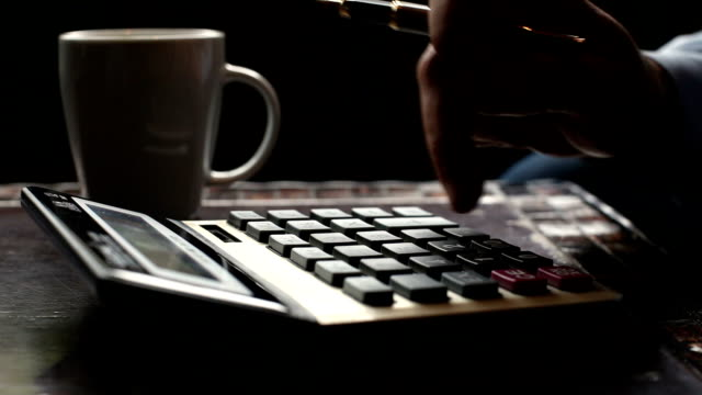Business man typing on calculator drinking coffee, tea video