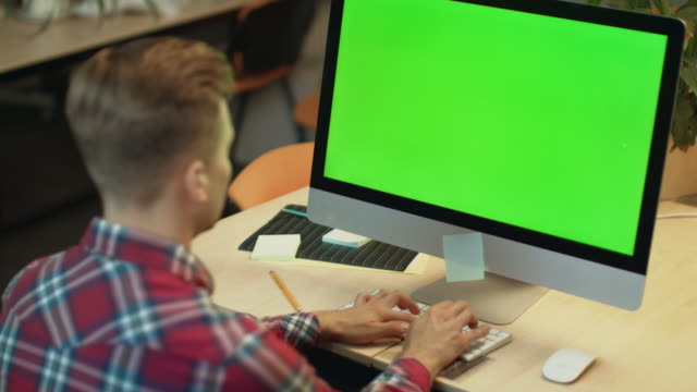 Video Business man typing on computer with green screen. Young man working on computer