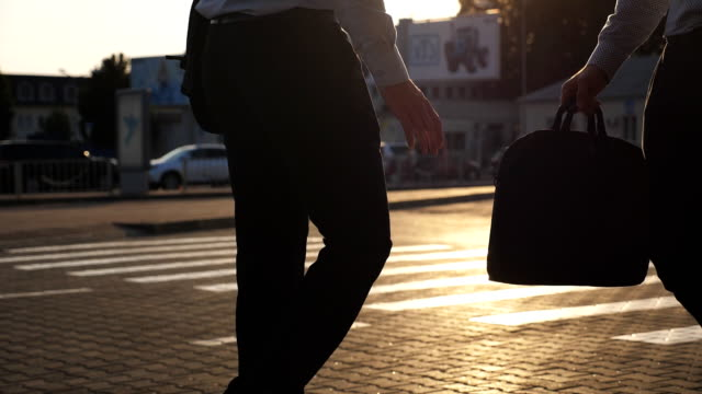 vídeos de stock e filmes b-roll de business man unnoticeably passing a black briefcase to his partner. unrecognizable colleagues in the city background. two young businessmen meeting outdoor. close up slow motion side view - corruption