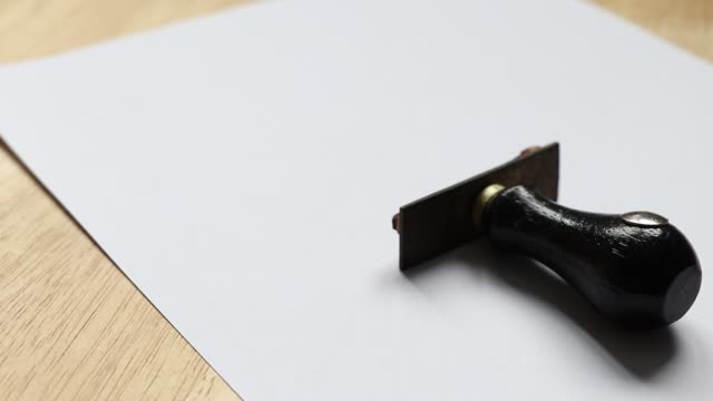 business man use the rubber stamp in to the blank paper background on wood table background - appalti pubblici video stock e b–roll