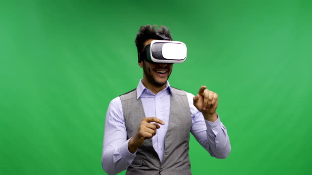Business Man Uses Virtual Reality Glasses Over Chroma Key Green Screen, Smiling Latin Businessman Touch Virtual Interface