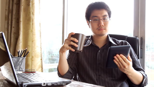business man using mobile tablet computer and drinking coffee at the table in office video