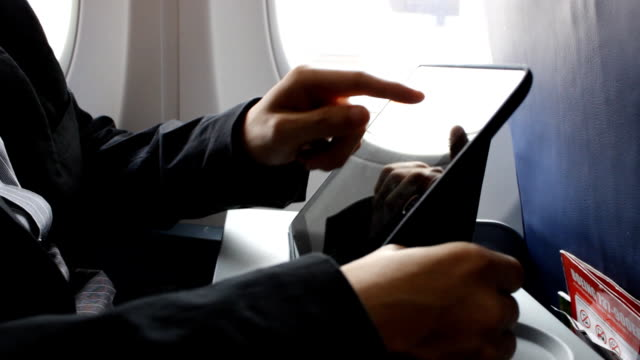 business man using tablet on the plane - sedili aereo video stock e b–roll
