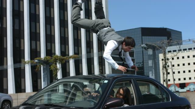 бизнес человек перелетает через машину на парковке - трюк стоковые видео и кадры b-roll
