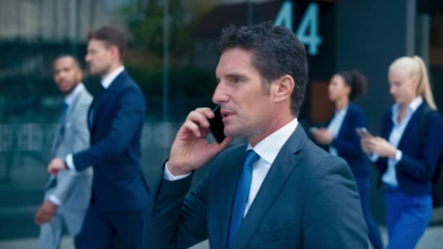 ビジネスビルに沿って歩き、電話で話す slo mo ts ビジネスマン - サラリーマン点の映像素材/bロール