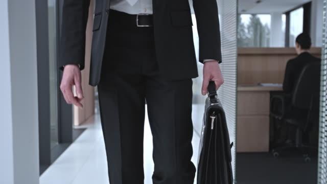 vídeos de stock, filmes e b-roll de slo mo ds homem de negócios, caminhando pelo corredor - plano médio