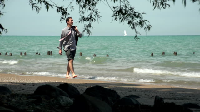 Business man walking happily on the beach video
