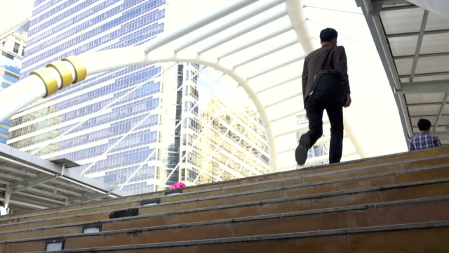 Business man walking up stairs to work in modern city video