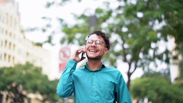 business man walking using mobile on the go - młodzi mężczyźni filmów i materiałów b-roll