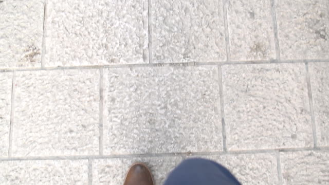 Business man walks along the way with blue slacks and brown leather shoe - view from first person on legs video