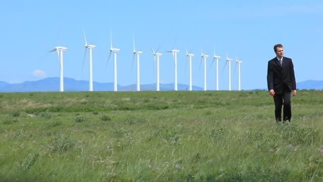 Business man walks with wind turbines