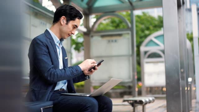 stockvideo's en b-roll-footage met business man met gehoorapparaat met behulp van laptop op bus station - oost azië
