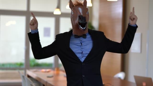 vídeos de stock, filmes e b-roll de homem de negócios com cavalo máscara dançando no escritório - festa da empresa