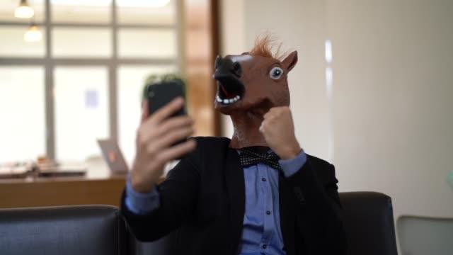 Homem de negócios com cavalo máscara tomando uma Selfie no escritório - vídeo