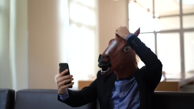 Business man with Horse Mask Taking a Selfie at Office