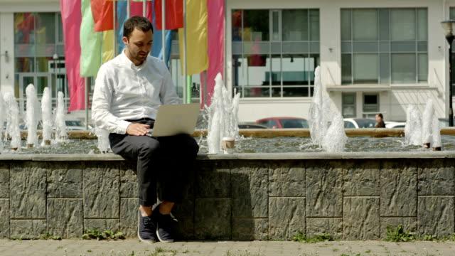 zakenman met laptop buiten op een bankje naast fontein werken video