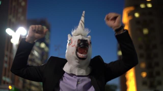 Homem de negócios com unicórnio máscara comemorando - vídeo